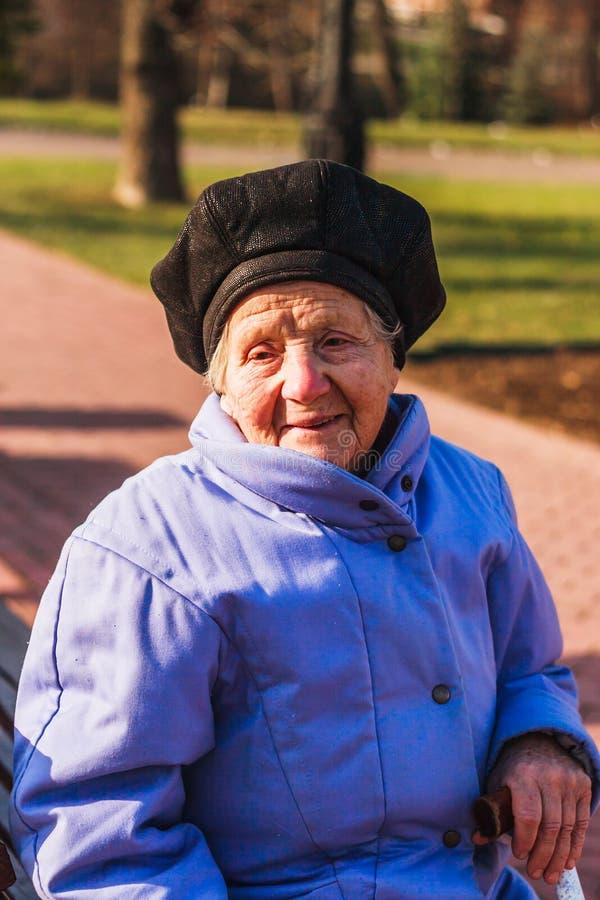 Dame âgée gaie s'asseyant avec un bâton photo libre de droits