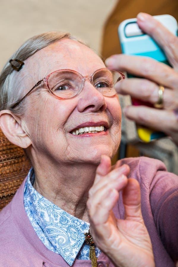 Dame âgée heureuse prenant Selfie photos stock