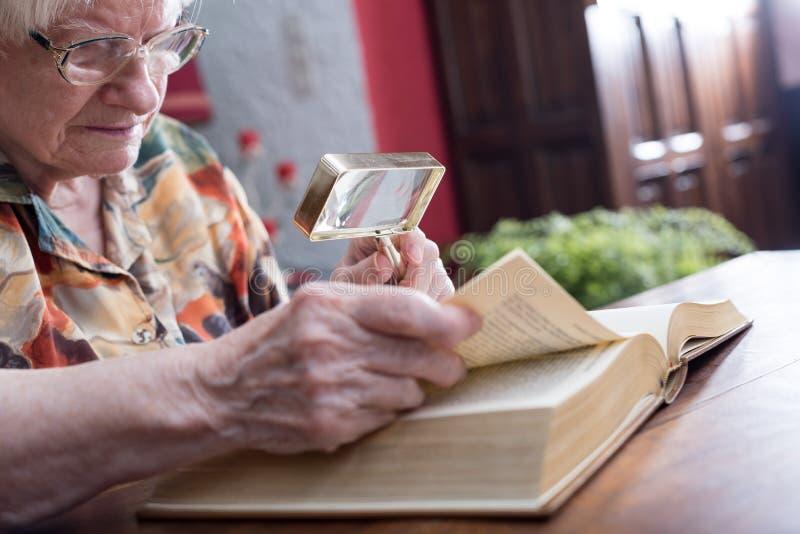 Dame âgée lisant un livre images libres de droits