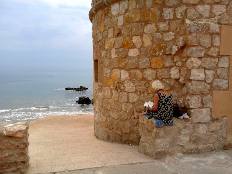 Dame âgée lit un livre se reposent sur un mur en pierre à côté de la mer et près de la tour de observation photo libre de droits