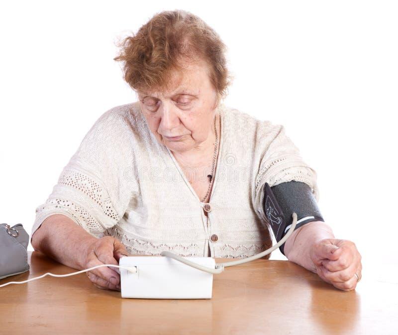Dame âgée mesure la pression artérielle au moment photos libres de droits