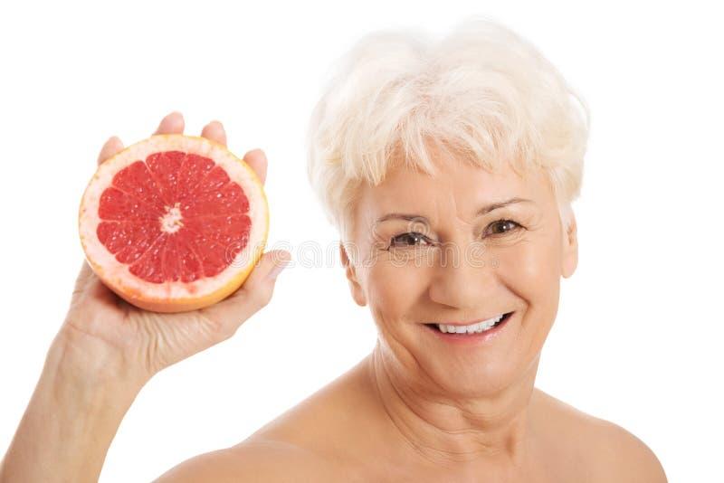 Dame âgée nue tenant un pamplemousse. images stock