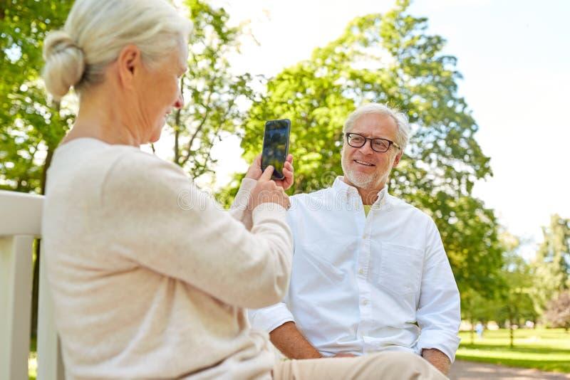Dame âgée photographiant l'homme par le smartphone en parc photo libre de droits
