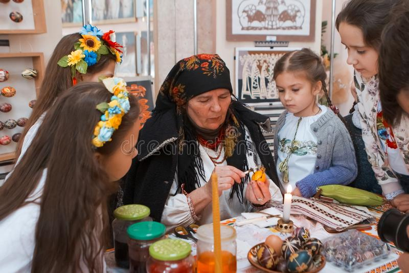 Dame âgée pysankar enseigne de petites filles à écrire un ornement folklorique floral sur le pysanka d'oeuf de pâques, Vinnytsia, images libres de droits