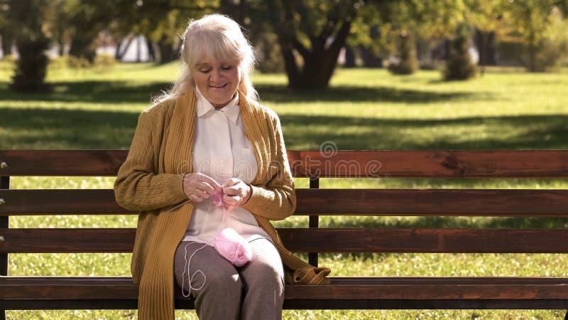 Dame âgée rêveuse tricotant de petites chaussettes pour sa petite-fille, générations de famille photographie stock