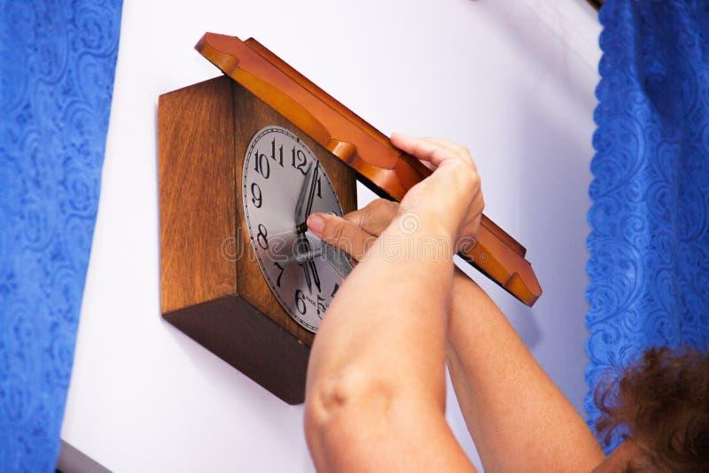 Dame âgée remonte la vieille horloge murale avec la clé Le symbole du passage du temps et l'alternance des générations images libres de droits