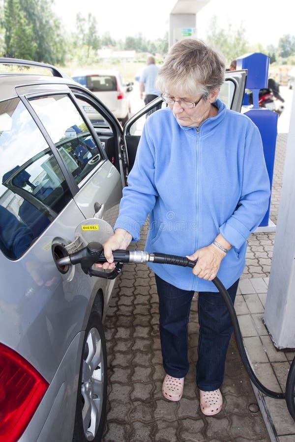 Dame âgée remplissant de combustible la voiture