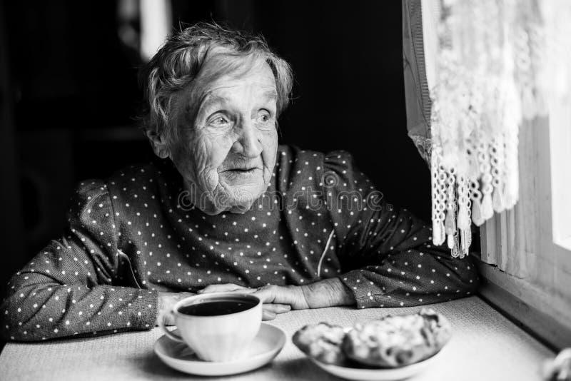 Dame âgée s'asseyant près du thé potable de fenêtre avec des petits pains photos libres de droits