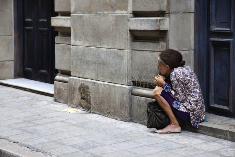 Dame âgée s'asseyant sur la rue de vieille La Havane photo libre de droits
