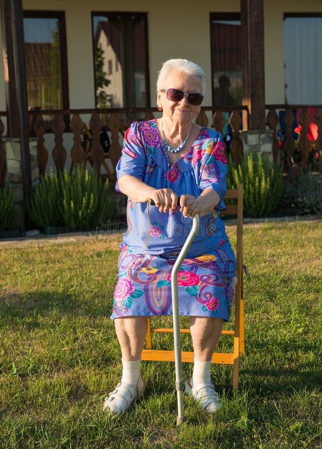 Dame âgée s'asseyant sur une chaise avec une canne images stock