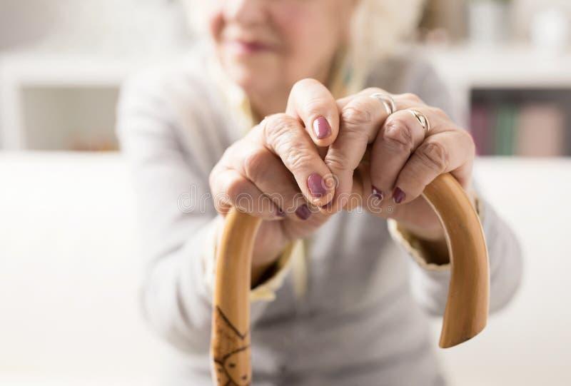 Dame âgée se tenant dessus sur le bâton de marche images stock