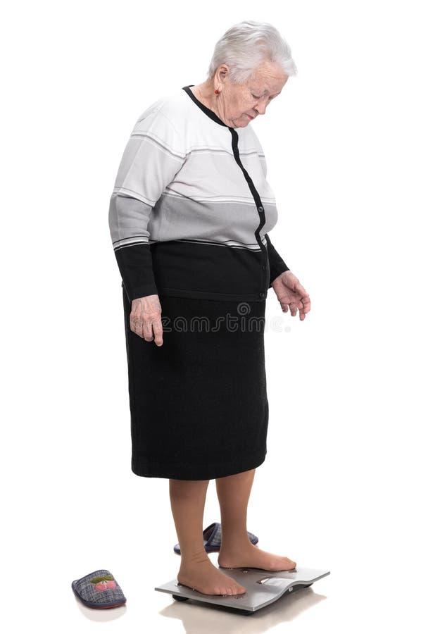 Dame âgée se tenant sur des échelles de salle de bains image libre de droits