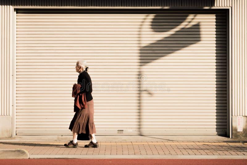 Dame âgée seule marche le long du bord de la route de Tokyo, Japon photographie stock libre de droits
