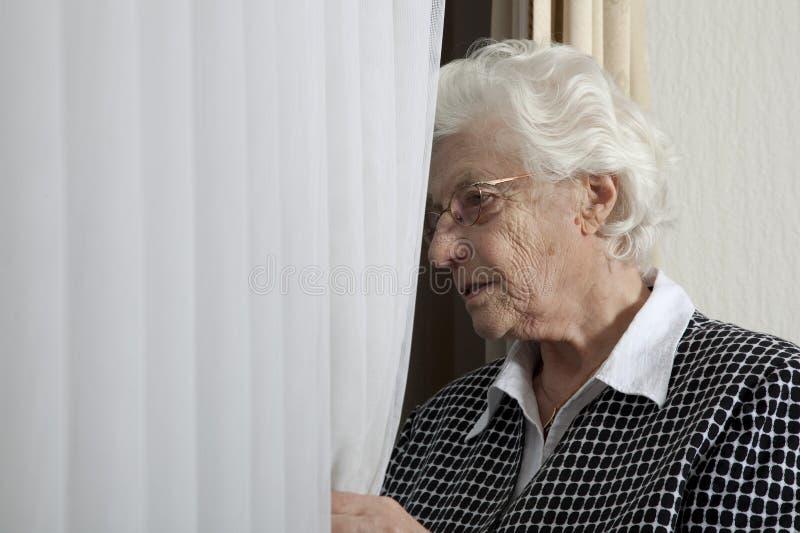 Dame âgée seule regardant hors de l'hublot images stock