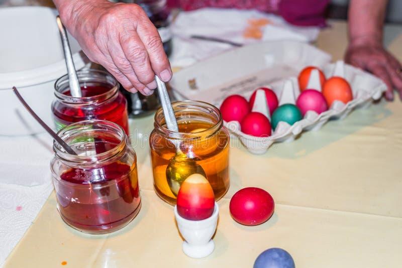Dame âgée teignant des oeufs de pâques à la maison dans la cuisine dans le verre de concombre et avec différentes couleurs, Allem photo stock