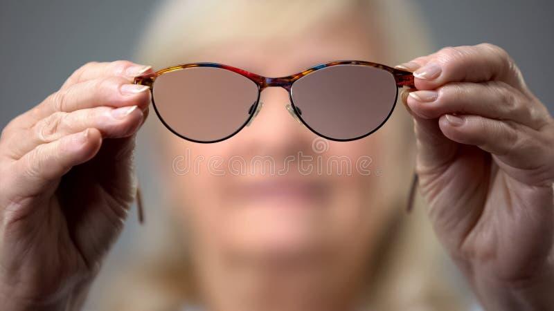 Dame âgée tenant les verres à la mode, concept des problèmes de vision, fond brouillé image stock