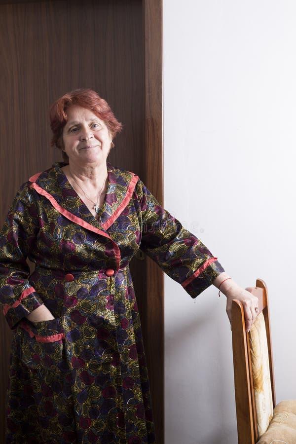 Dame âgée tout près une porte en bois brune photo stock
