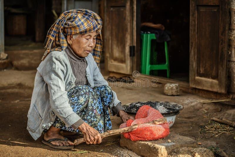 Dame âgée travaillant devant sa maison photo libre de droits