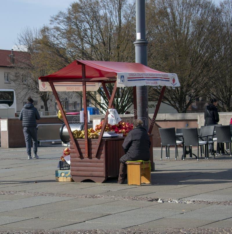 Dame âgée vendant des fruits et légumes sur la place images libres de droits