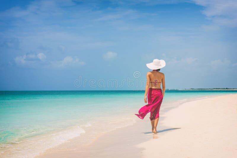 Dame élégante de vacances de luxe de voyage marchant sur la plage dans l'enveloppe rose de jupe de mode détendant des vacances de image stock
