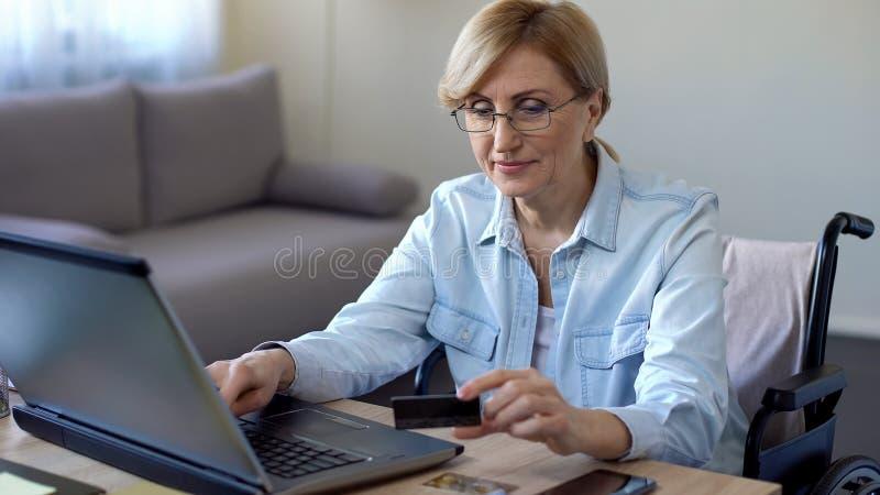 Dame adulte sérieuse dans le numéro de carte entrant de fauteuil roulant sur l'ordinateur portable, faisant des emplettes en lign photo stock