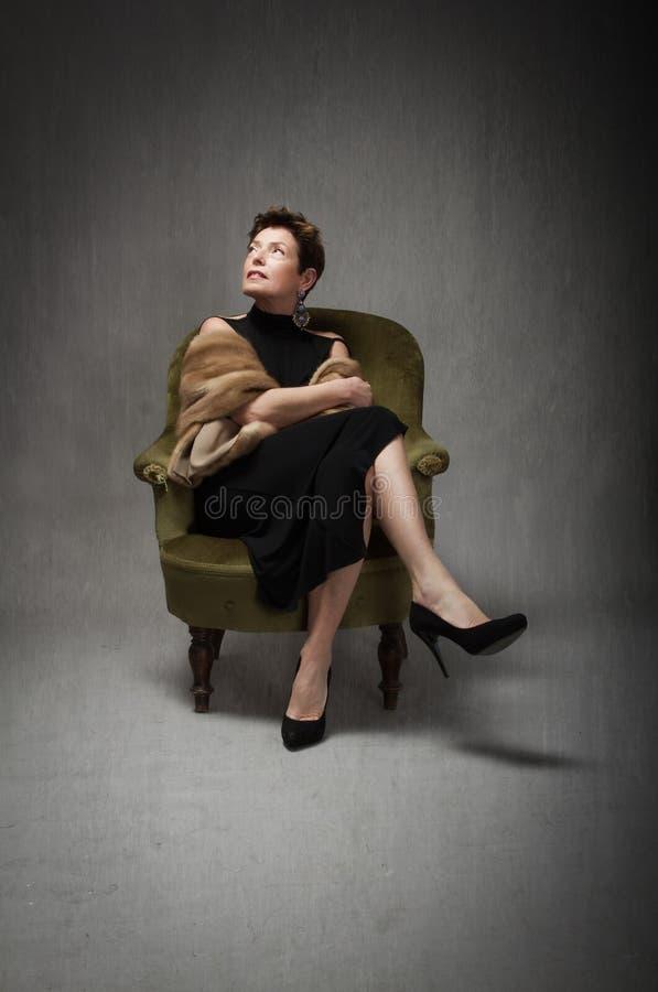Dame adulte s'asseyant sur le sofa photographie stock