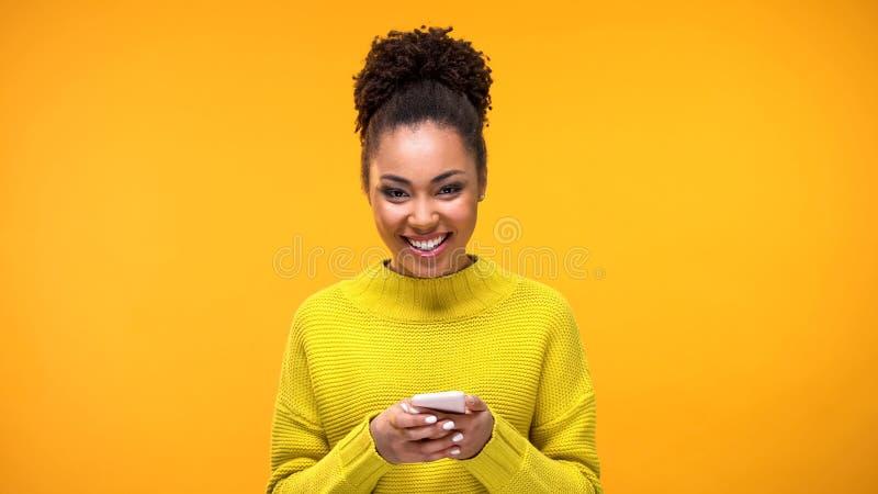 Dame afro-américaine excitée souriant sur la main de téléphone de caméra, message de réseau social photos stock