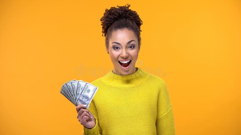 Dame afro-américaine heureuse montrant le groupe de dollars sur la caméra, le travail haut-payé photo stock