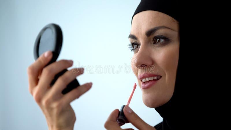 Dame arabe attirante appliquant le lustre de l?vre, souriant dans le miroir, soin de visage, maquillage photos stock