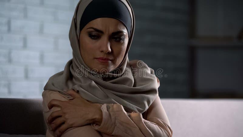 Dame arabe bouleversée dans le hijab tenant la main douloureuse, assaut dans la famille, problème social photo stock