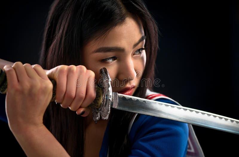 Dame asiatique avec l'épée dans le studio image stock