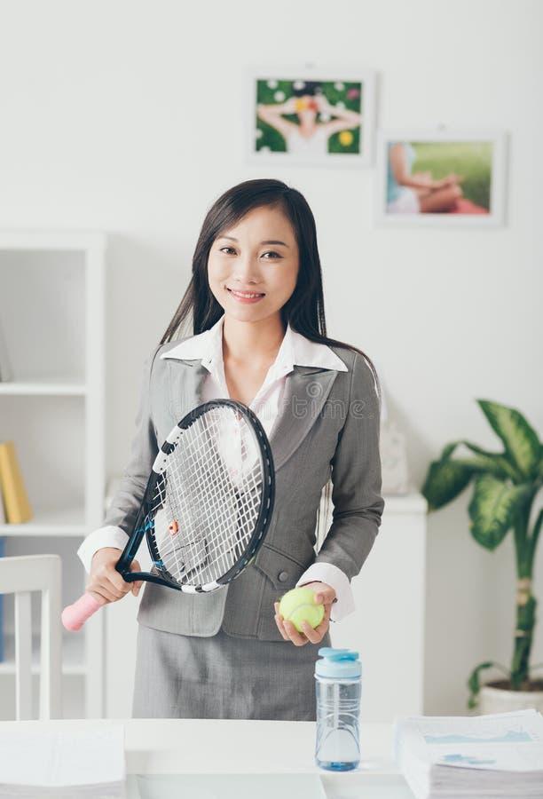 Dame asiatique d'affaires avec la raquette de tennis photographie stock libre de droits