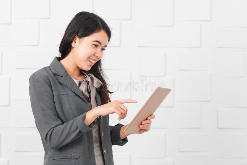Dame asiatique dans le tenue professionnelle d?contract?e, comprim? ? disposition image stock