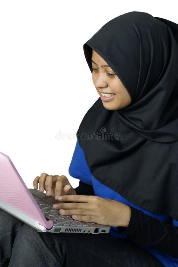 Dame asiatique musulmane heureuse à l'aide de l'ordinateur portatif image stock