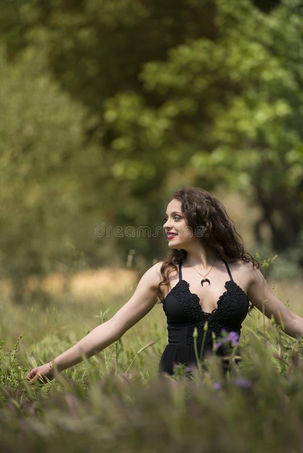 Dame assez jeune parmi le grand champ de mauvaises herbes image stock