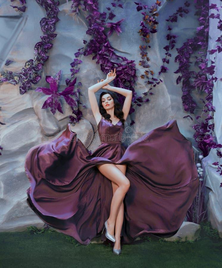 Dame attirante mince comme l'image de l'artiste magnifique, longue robe pourpre de flottement volante de satin comme des courses  images libres de droits