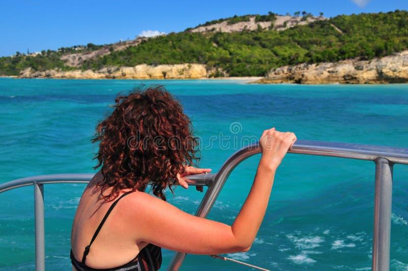Dame auf einem Boot, das eine Insel betrachtet stockfotografie