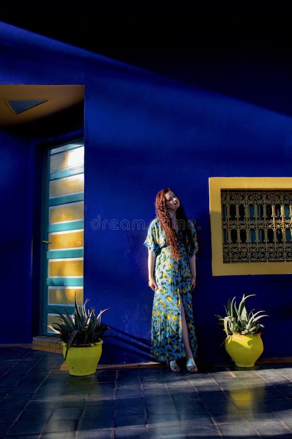 Dame aux cheveux longs posant sur une terrasse bleue et jaune image libre de droits