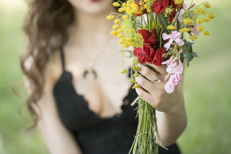 Dame bietet Ihnen einen Blumenstrauß von wilden Blumen an stockfotografie