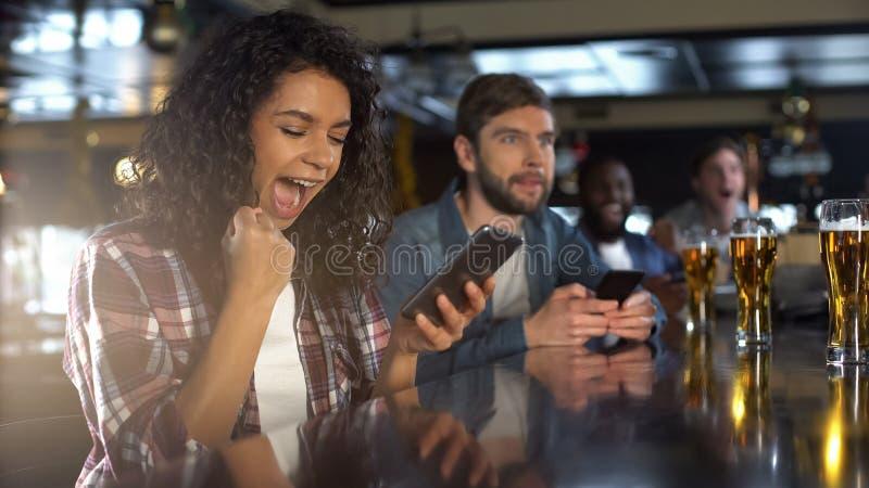 Dame biracial gaie dans le bar célébrant le pari réussi sur des sports, appli en ligne photos libres de droits