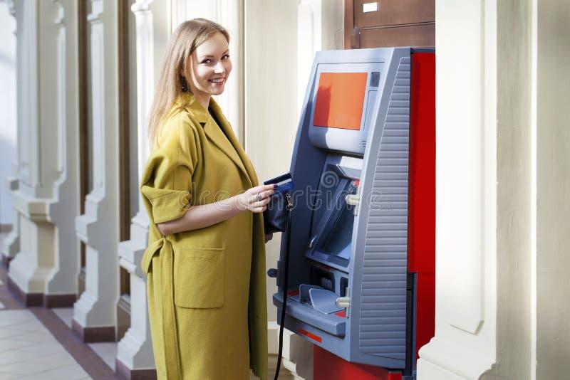 Dame blonde à l'aide d'un distributeur automatique images libres de droits