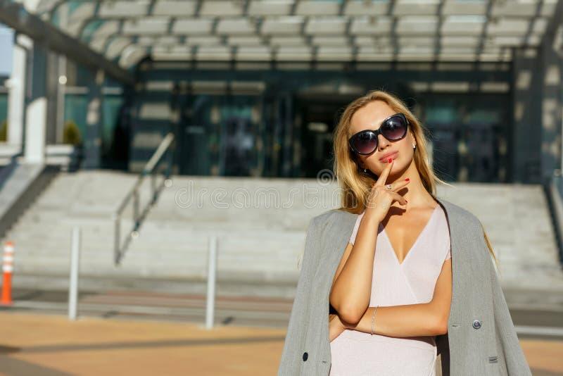 Dame blonde étonnante en verres élégants posant à l'avenue dans s photos stock