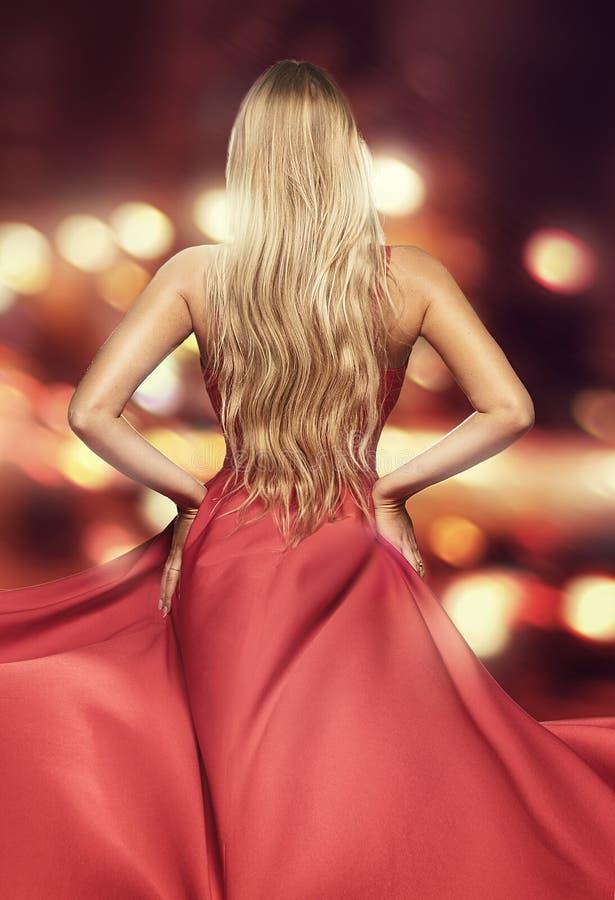 Dame blonde dans la maxi robe élégante rouge photo stock