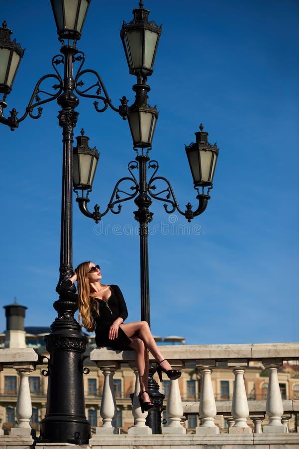 Dame blonde dans la robe noire se reposant sur la balustrade de balustre sous le réverbère de vintage photographie stock