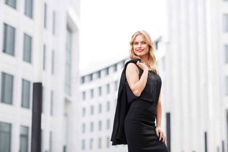 Dame blonde dans le chemisier noir et la jupe tenant le bureau proche photo libre de droits