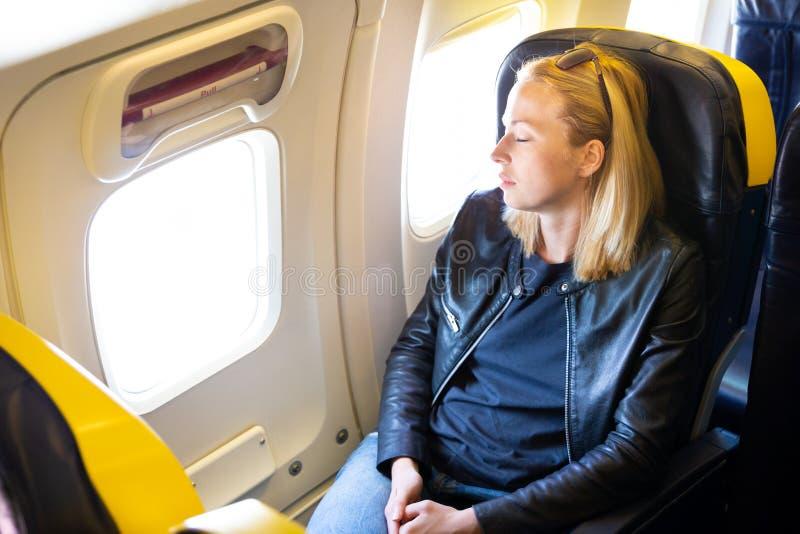 Dame caucasienne occasionnelle blonde fatiguée faisant une sieste sur le siège tout en voyageant en avion photos stock
