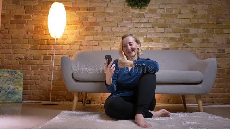 Dame caucasienne supérieure heureuse parlant dans le videochat sur le signe de doigt- d'apparence de smartphone en atmosphère à l images stock