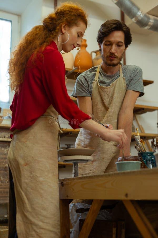 Dame curieuse avec la coiffure sauvage apprenant la maîtrise de poterie photographie stock