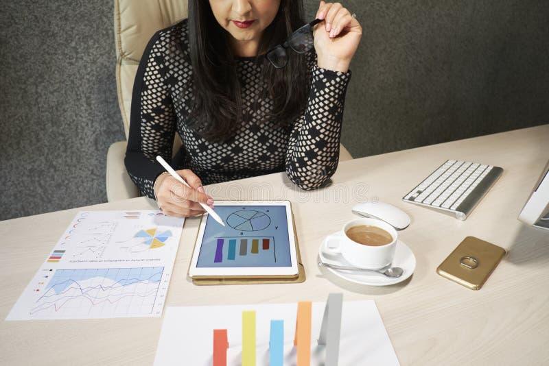 Dame d'affaires analysant des statistiques financières photo stock