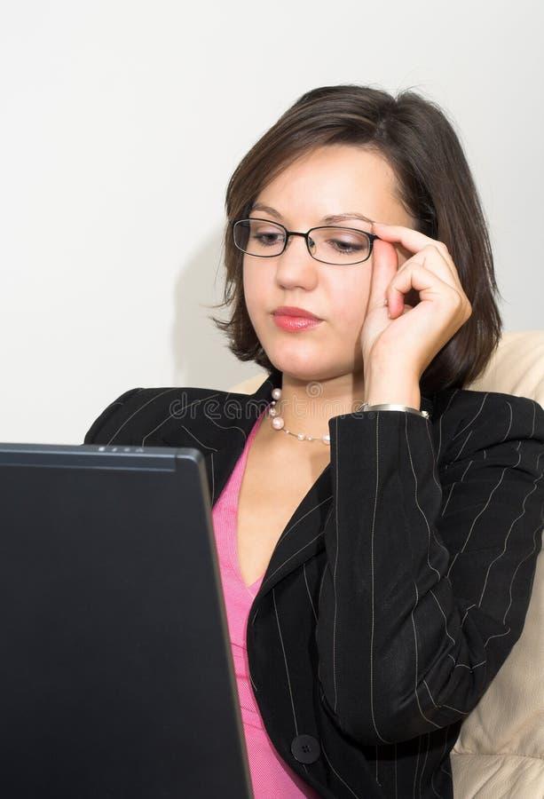 Dame d'affaires avec un ordinateur portatif touchant ses glaces photo stock